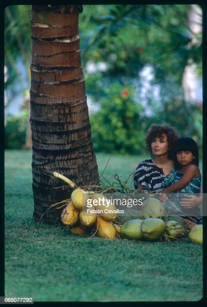 Marlene Jobert sits by coconuts and holds a child while on vacation in Mauritius