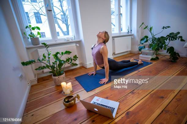 Marlene of Yoga on the Move Berlin warms up prior online stream session in her home on March 25 2020 in Berlin Germany Small businesses are trying...