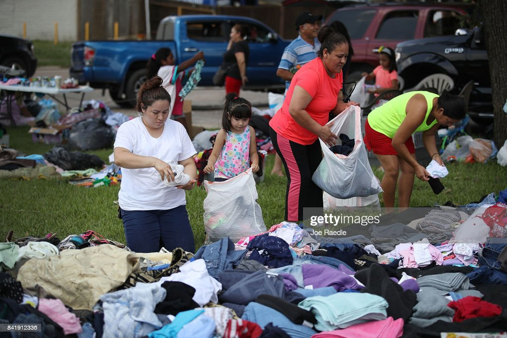 Marlet Rodriguez and her daughter, Nadia Jimenez, look through donated clothes after their home was inundated with flood waters during Hurricane and Tropical Storm Harvey on September 2, 2017 in Houston, Texas. The donations were brought into the neighborhood by a family that drove from Dallas to help out. Harvey, which made landfall north of Corpus Christi on August 25, dumped around 50 inches of rain in and around areas of Houston and Southeast Texas.