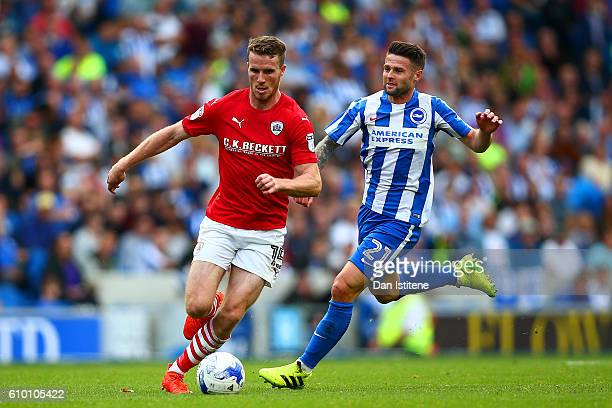 Marley Watkins of Barnsley runs with the ball under pressure from Oliver Norwood of Brighton & Hove Albion during the Sky Bet Championship match...