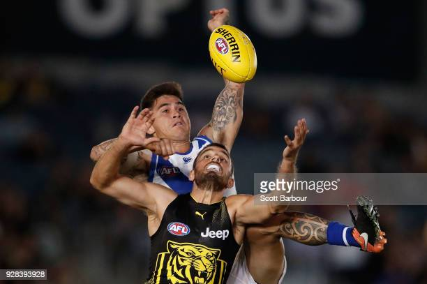 Marley Williams of the Kangaroos and Sam Lloyd of the Tigers compete for the ball during the AFL JLT Community Series match between the Richmond...