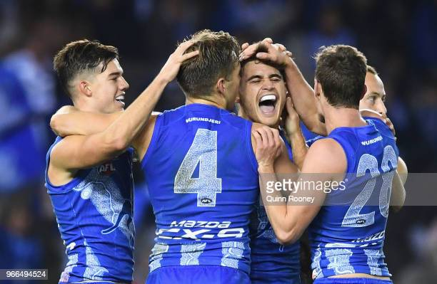 Marley Williams of the Kangaroos is congratulated by team mates after kicking a goal during the round 11 AFL match between the North Melbourne...