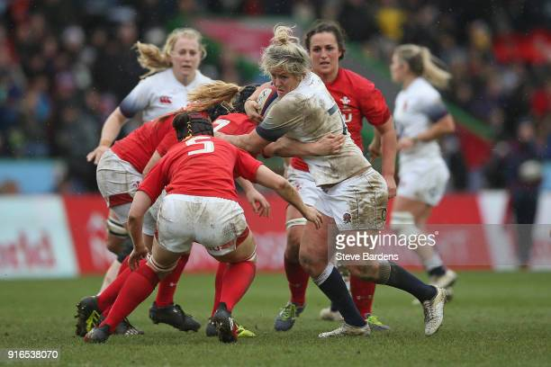 Marlie Packer of England Women is tackled by Beth Lewis of Wales Women during the Natwest Women's Six Nations Championships match between England and...