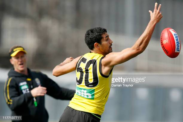 Marlion Pickett of the Tigers gathers the ball as senior coach, Damien Hardwick looks on during a Richmond Tigers AFL training session at Punt Road...