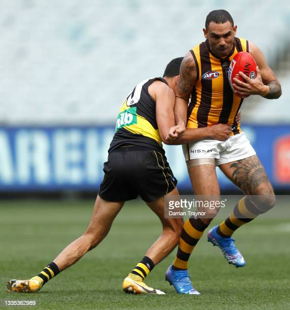 Marlion Pickett of the Tigers tackles Shaun Burgoyne of the Hawks during the round 23 AFL match between Richmond Tigers and Hawthorn Hawks at...