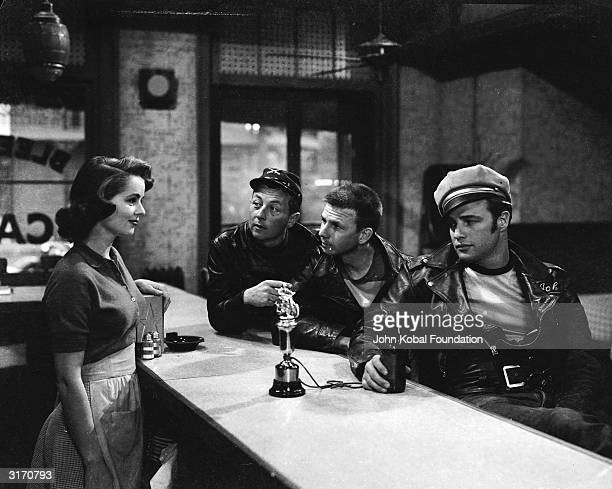 Marlon Brando and fellow motorcycle gang members try to impress barmaid Mary Murphy with their trophy in a scene from 'The Wild One' directed by...