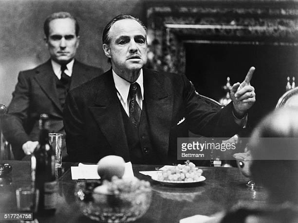 Marlon Brando as Don Vito Corleone in The Godfather, for which he won an Oscar for Best Actor. Behind him is Robert Duvall, playing Tom Hagen, the...