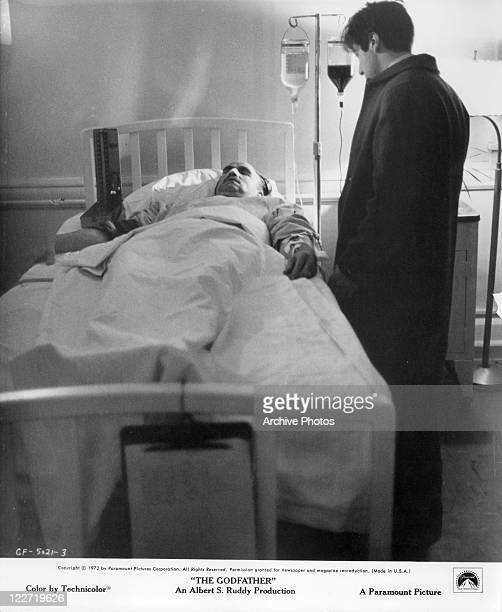 Marlon Brando lays in bed as Al Pacino stands beside him in a scene from the film 'The Godfather' 1972