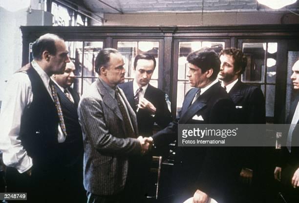 Marlon Brando shakes hands with Al Lettieri while Abe Vigoda Richard S Castellano John Cazale James Caan and Robert Duvall look on in a still from...