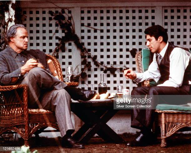 Marlon Brando , US actor, sitting opposite Al Pacino, US actor, both sitting on wicker garden chairs, in a publicity still issued for the film, 'The...