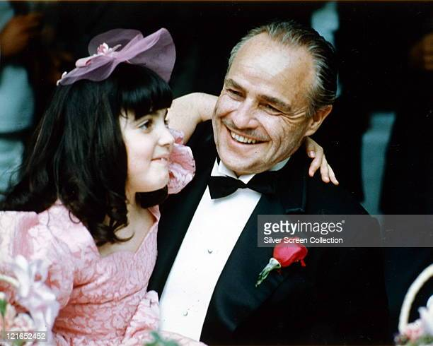 Marlon Brando US actor smiling and wearing a black dinner suit with a white shirt with wingtip collars and a black bow tie with a young girl in a...