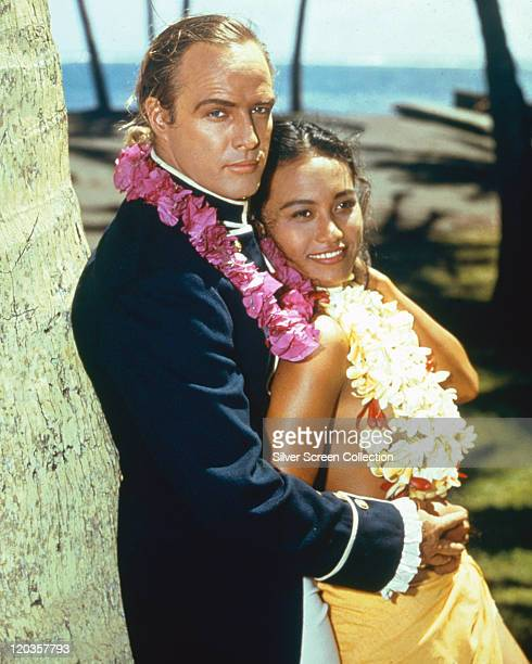 Marlon Brando US actor with Tarita Teriipia French Polynesian actress both wearing floral garlands in a publicity portrait issued for the film...
