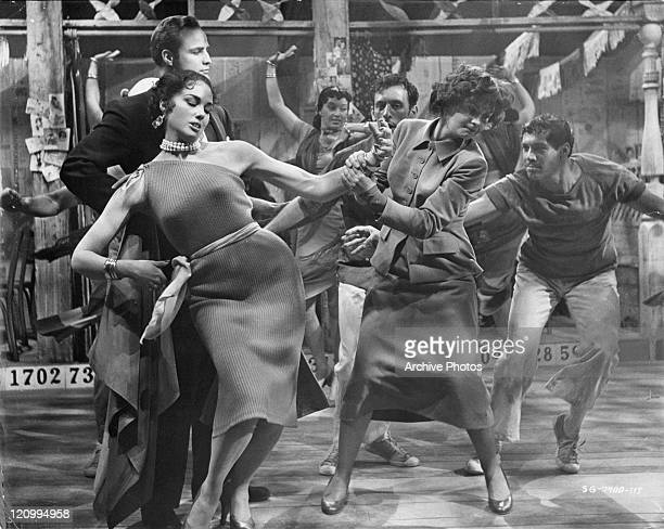 Marlon Brando watches as Jean Simmons tries to drag away another woman in a scene from the film 'Guys And Dolls' 1955