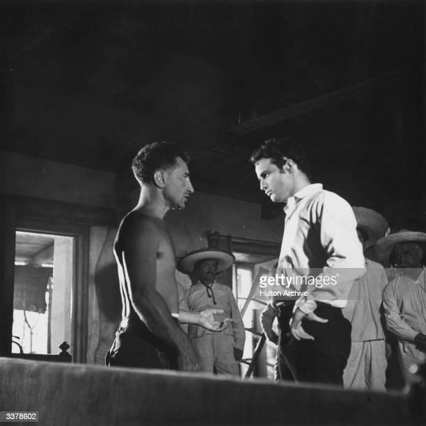 Marlon Brando, who plays Mexican folk hero Emiliano Zapata, talks to director Elia Kazan on the set of 'Viva Zapata!', written by John Steinbeck and...