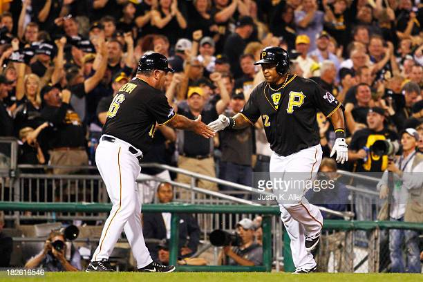 Marlon Byrd celebrates his second inning home run with third base coach Nick Leyva of the Pittsburgh Pirates during their National League Wild Card...