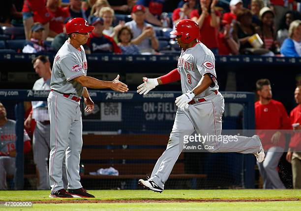 Marlon Byrd of the Cincinnati Reds celebrates his solo homer in the sixth inning against the Atlanta Braves with third base coach Jim Riggleman at...