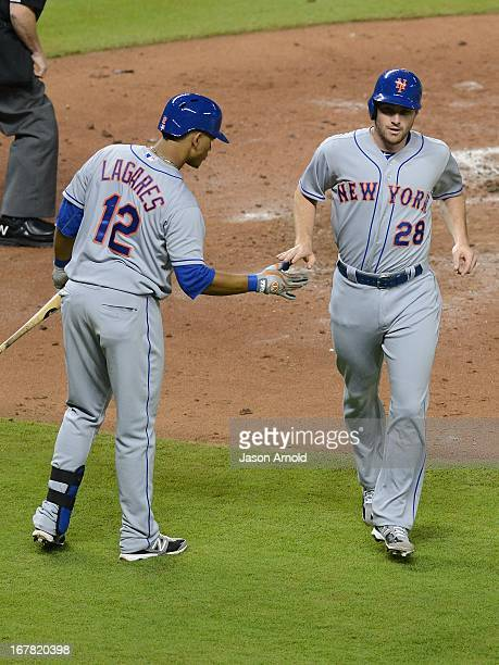 Marlon Byrd of the New York Mets celebrates scoring a run against the Miami Marlins with teammate Collin Cowgill at Marlins Park on April 30 2013 in...
