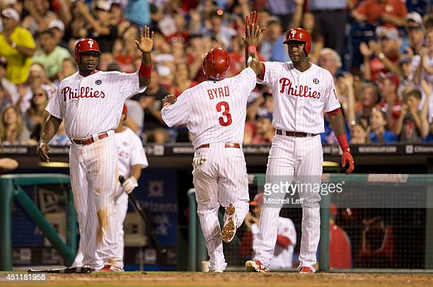 Marlon Byrd of the Philadelphia Phillies high fives Ryan Howard and John Mayberry Jr #15 after scoring a run in the bottom of the sixth inning...