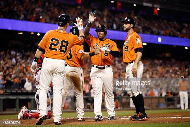 Marlon Byrd of the San Francisco Giants is congratulated by Buster Posey Nori Aoki and Brandon Belt after he hit a grand slam home run that scored...