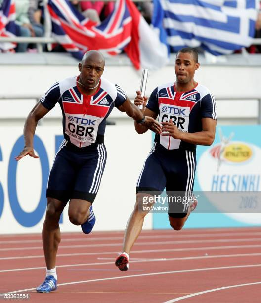 Marlon Devonish of Great Britain hands over the baton to his teammate Christian Malcolm during the heats of the men's 4x100 Metres Relay at the 10th...