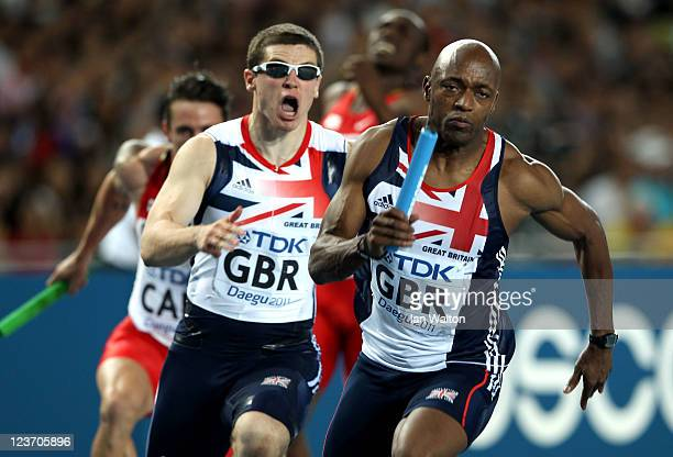 Marlon Devonish of Great Britain races awy after receiving the relay baton from Craig Pickering in the men's 4x100 metres relay heats during day nine...