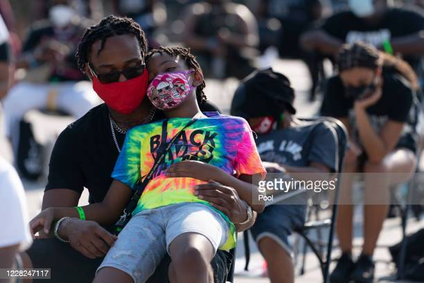 Marlon Holmes, of Chicago, holds his daughter Victoria Mone on his lap as they await the start of the March on Washington at the Lincoln Memorial on...