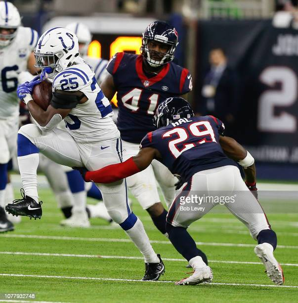 Marlon Mack of the Indianapolis Colts runs past Andre Hal of the Houston Texans and Zach Cunningham during the third quarter during the Wild Card...
