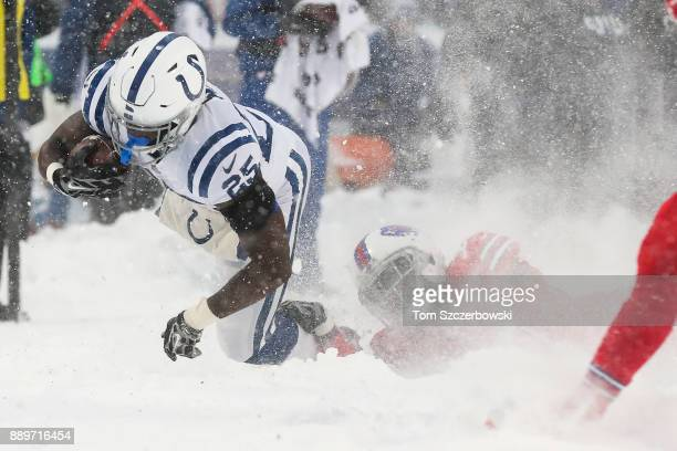 Marlon Mack of the Indianapolis Colts runs the ball as Tre'Davious White of the Buffalo Bills attempts to tackle him during the fourth quarter...