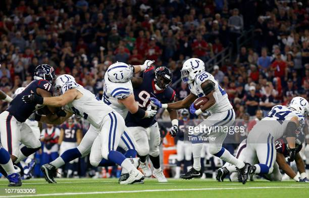 Marlon Mack of the Indianapolis Colts runs the ball in the fourth quarter defended by DJ Reader of the Houston Texans and Zach Cunningham during the...