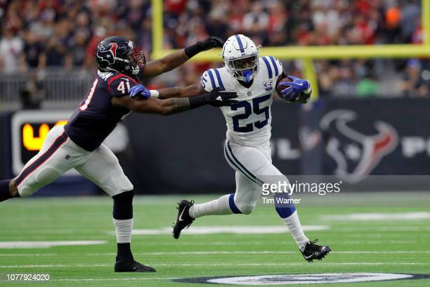 Marlon Mack of the Indianapolis Colts runs the ball in the second quarter defended by Zach Cunningham of the Houston Texans during the Wild Card...