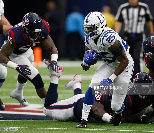 Marlon Mack of the Indianapolis Colts rushes past the tackle attempt of DJ Reader of the Houston Texans during the Wild Card Round at NRG Stadium on...