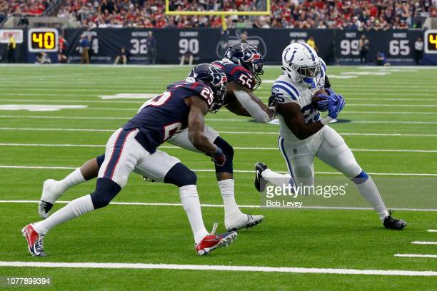 Marlon Mack of the Indianapolis Colts rushes the ball defended by Kareem Jackson and Benardrick McKinney of the Houston Texans in the first quarter...