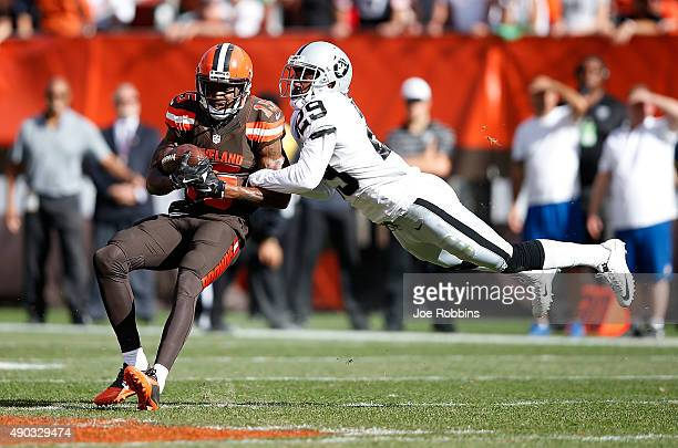 Marlon Moore of the Cleveland Browns makes a catch in front of David Amerson of the Oakland Raiders during the fourth quarter at FirstEnergy Stadium...