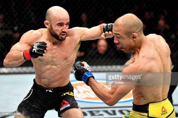 Marlon Moraes of Brazil punches Jose Aldo of Brazil in their bantamweight bout during the UFC 245 event at T-Mobile Arena on December 14, 2019 in Las...