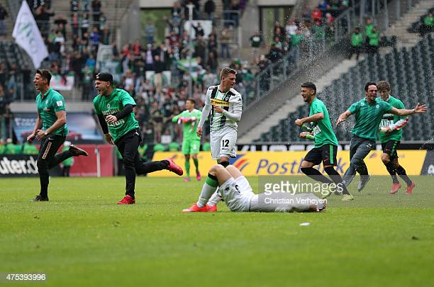 Marlon Ritter and Christopher Lenz of Borussia Moenchengladbach are frustrated on the ground while players of Werder Bremen celebrate after the 3...