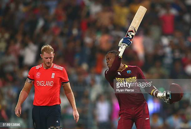 Marlon Samuels of the West Indies celebrates after Carlos Brathwaite of the West Indies hit the second six of the last over as Ben Stokes of England...