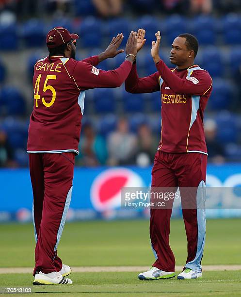 Marlon Samuels of the West Indies celebrates with teammate Chris Gayle after dismissing Hashim Amla of South Africa during the ICC Champions Trophy...