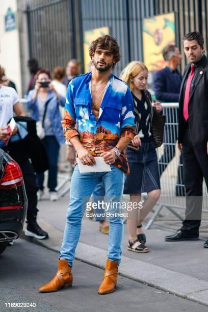 Marlon Teixeira wears necklaces, a landscape photo print shirt, rings, bracelets, blue denim pants, gold leather boots , outside Balmain, during...