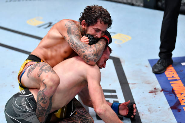 Marlon Vera of Ecuador secures a rear choke submission against Davey Grant of England in a bantamweight bout during the UFC Fight Night event at UFC...
