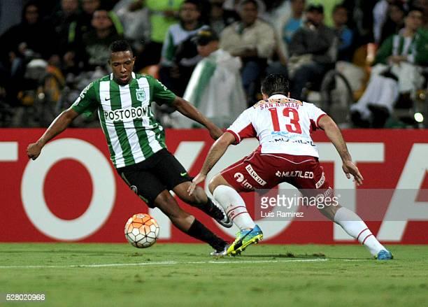 Marlos Moreno of Atletico Nacional vies for the ball with Jose San Roman of Huracan during a second leg match between Atletico Nacional and Huracan...
