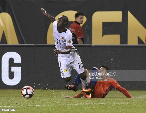 Marlos Moreno of Colombia falls down after the slide by Edson Puch of Chile during a Semifinal match between Colombia and Chile at Soldier Field as...