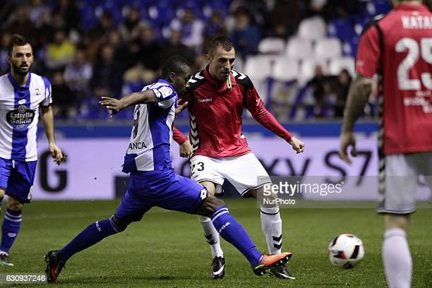 Marlos Moreno of Deportivo de La Coruna compete for the ball against Nenad Krsticic of Deportivo Alaves SAD during the spanish 1/8 Copa del Rey match...