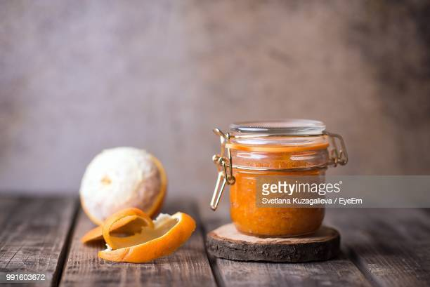 Marmalade In Jar By Orange On Table At Home