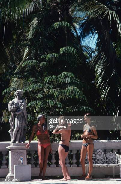 Marni Morrell and Denise Schluscer with a third woman all wearing bikinis pose beside a statue on a bridge in Haiti in January 1975