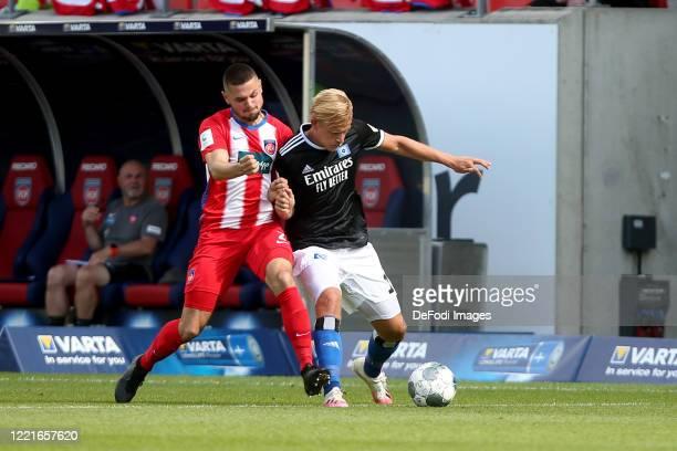 Marnon Busch of 1.FC Heidenheim 1846 and Joel Pohjanpalo of Hamburger SV battle for the ball during the Second Bundesliga match between 1. FC...