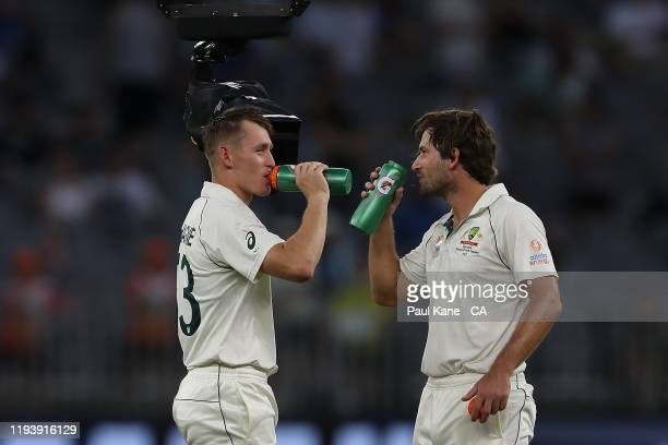 Marnus Labuschagne and Joe Burns of Australia talk to tv commentators via the Flying Fox camera at a drinks break during day three of the First Test...