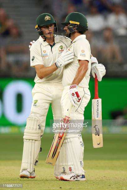 Marnus Labuschagne of Australia celebrates with Joe Burns of Australia after reaching his half century during day three of the First Test match in...