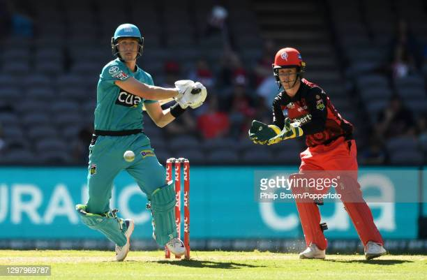 Marnus Labuschagne of Heat hits out watched by Sam Harper of Renegades during the Big Bash League match between the Melbourne Renegades and the...