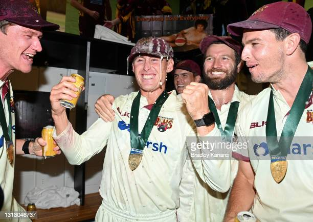 Marnus Labuschagne of Queensland celebrates victory with team mates Brendan Doggett and Jack Wildermuth after day four of the Sheffield Shield Final...