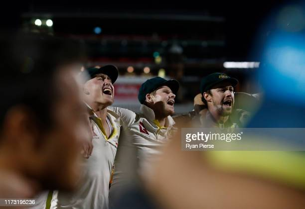 Marnus Labuschagne, Steve Smith and Travis Head of Australia celebrate with team mates while singing the team song on the pitch after Australia...